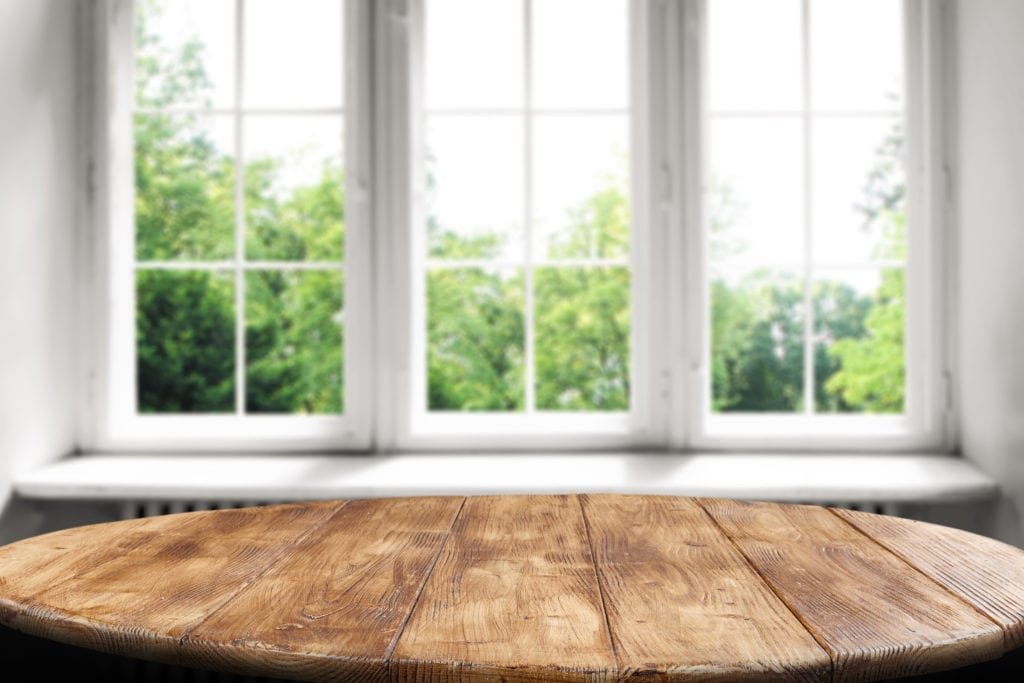 Table with windows in background for pella