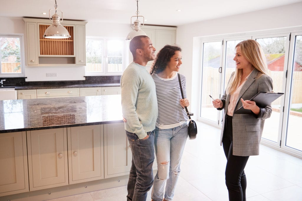 Realtor showing a house for sale to a couple, standing in kitchen