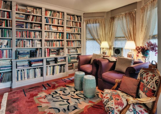 Living room with bookcases and colorful rug