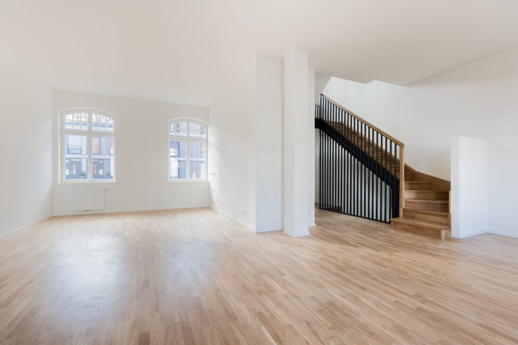 Empty home with reclaimed hardwood floors and wood staircase