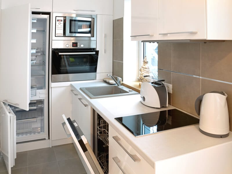 Small kitchen with open appliances.