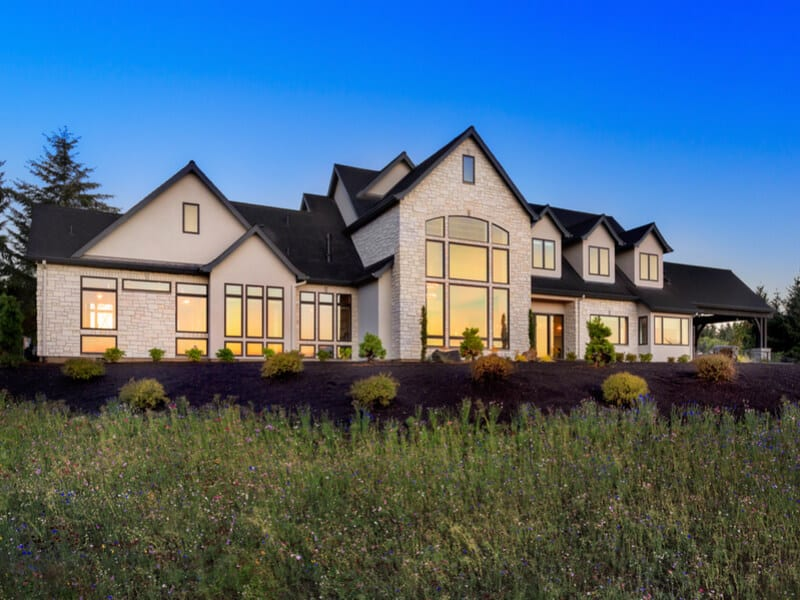 Home with large windows in grassy landscape
