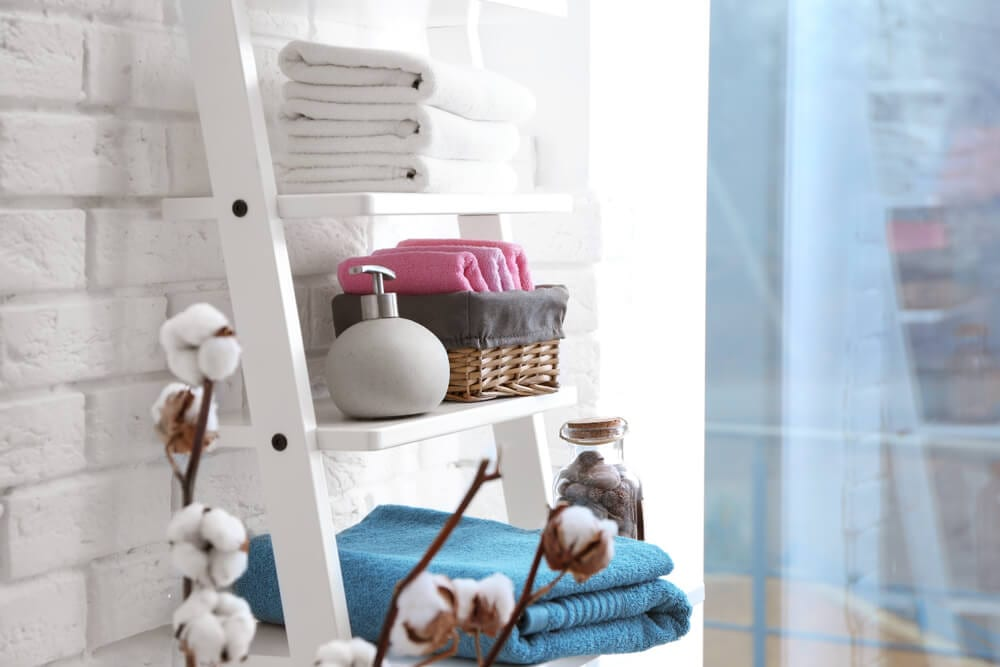Towels and other items stored on ladder shelf in bathroom