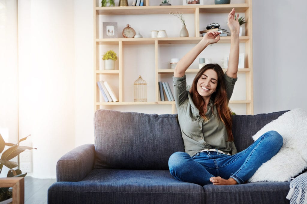 Shot of a happy young woman dancing while sitting on her sofa at home