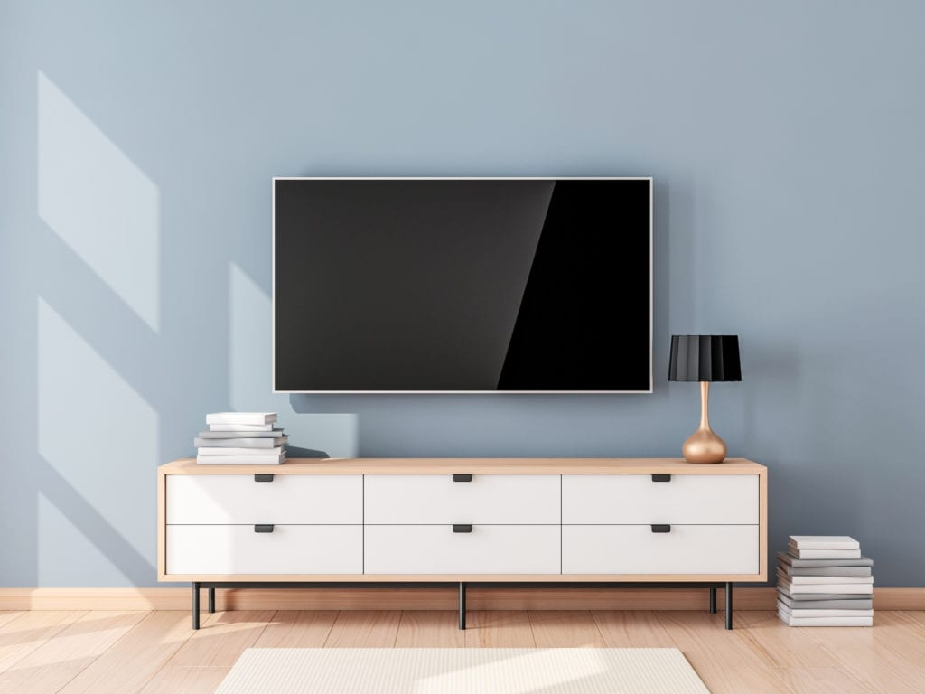 Modern TV and TV stand against blue wall in living room