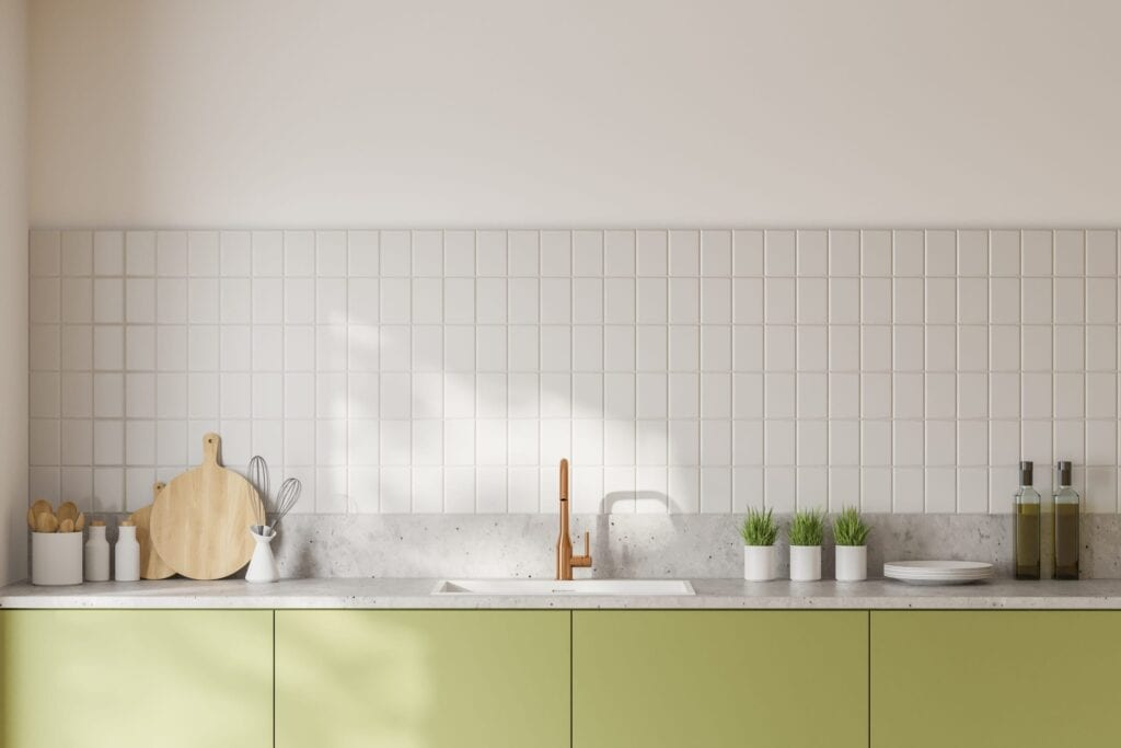 Green kitchen cabinets against modern gray tile backsplash