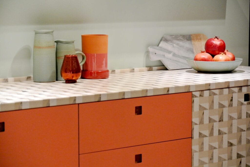 Kitchen counter with patterned top and orange cabinets