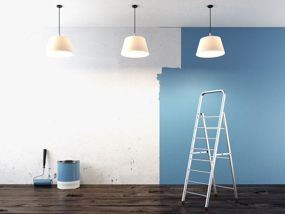 Wall half painted blue, ladder and paint bucket