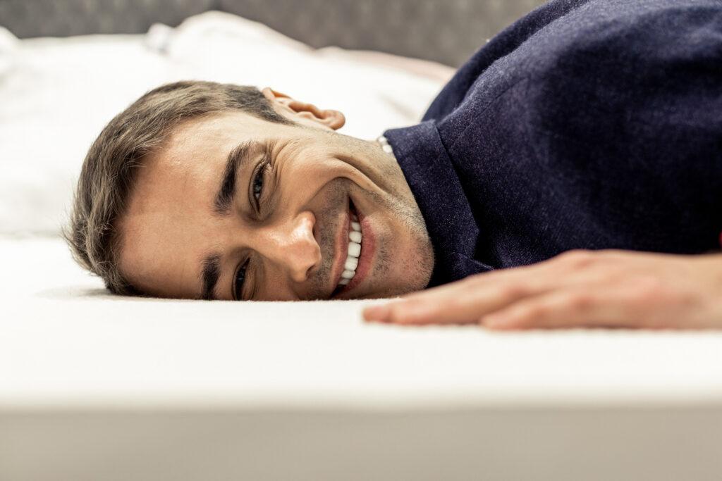 Man lies on a memory foam mattress