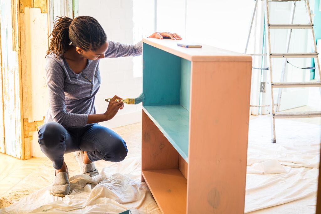 Young woman paints bookshelf