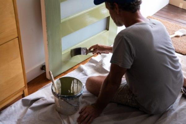 Man paints his front door