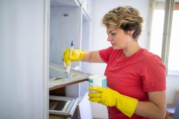 Woman with hands in gloves painting cabinet glass door white, redecorating in isolation during Covid-19 pandemic outbreak