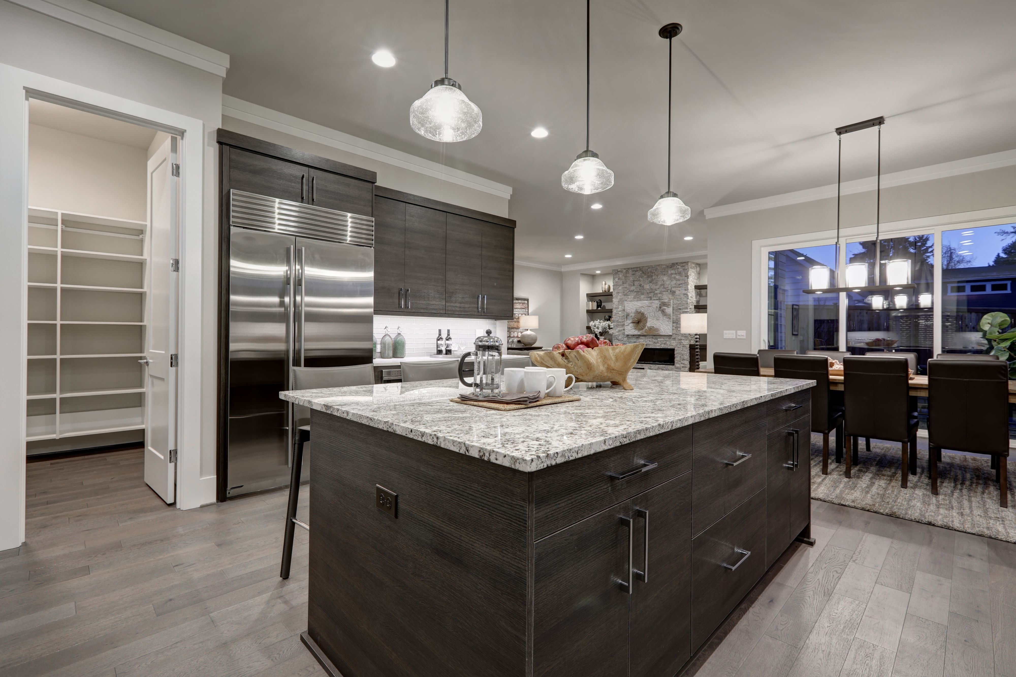 Luxury kitchen with dark gray cabinets on island, and modern light fixtures