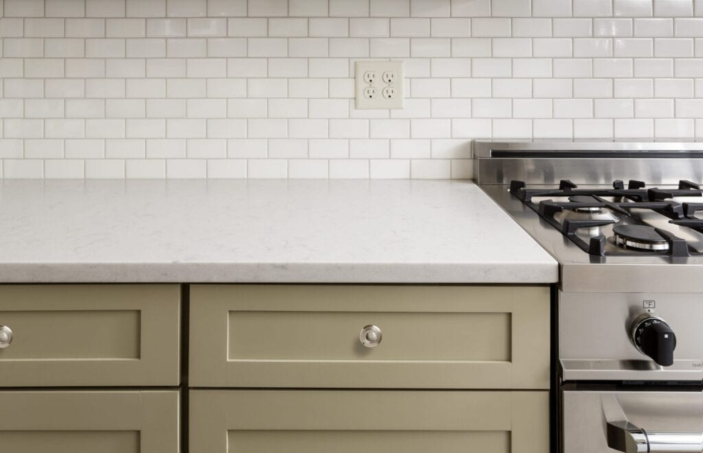 Khaki green kitchen cabinets with white subway tile backsplash