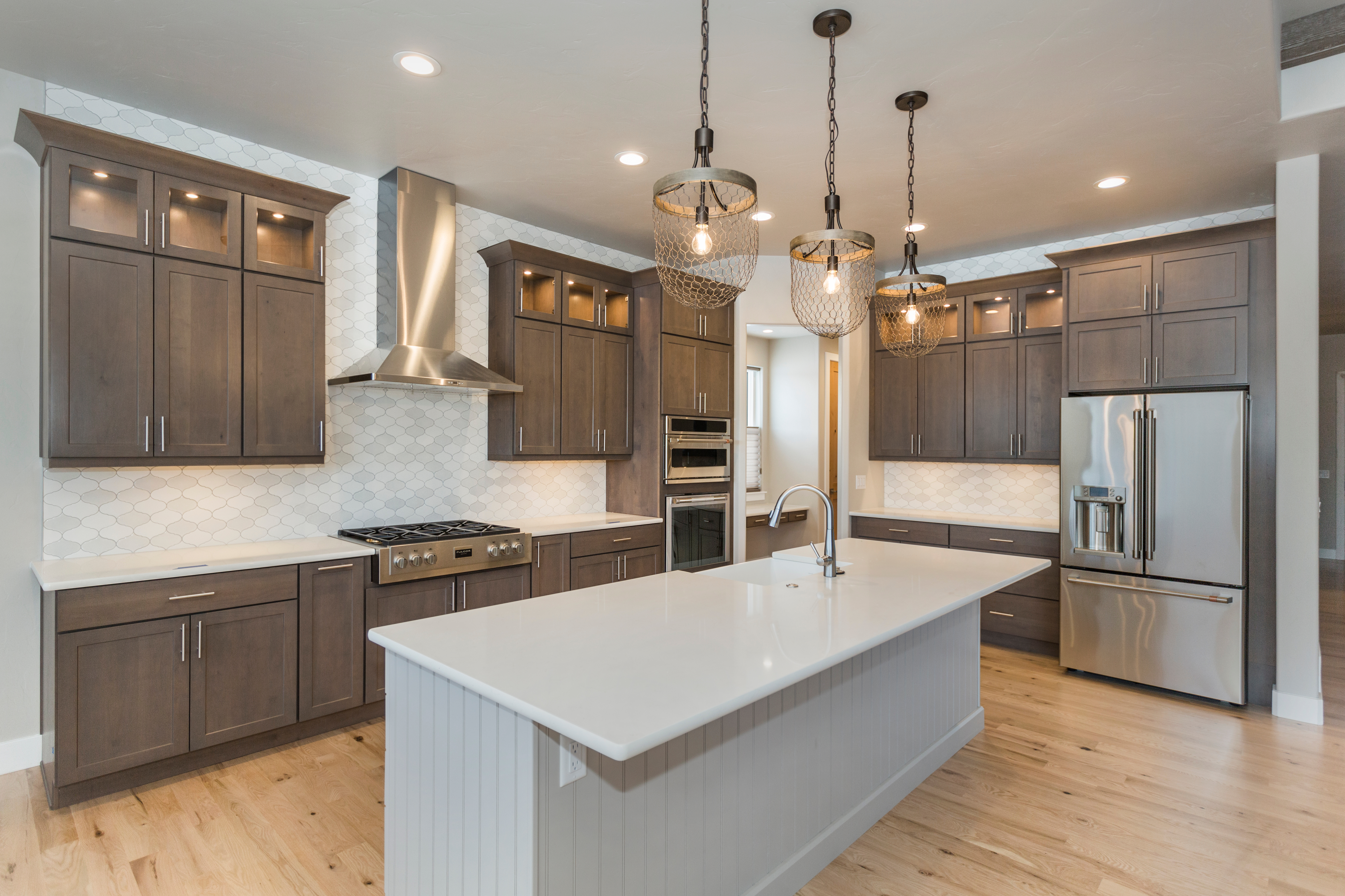 Luxury kitchen with island in center and taupe cabinets