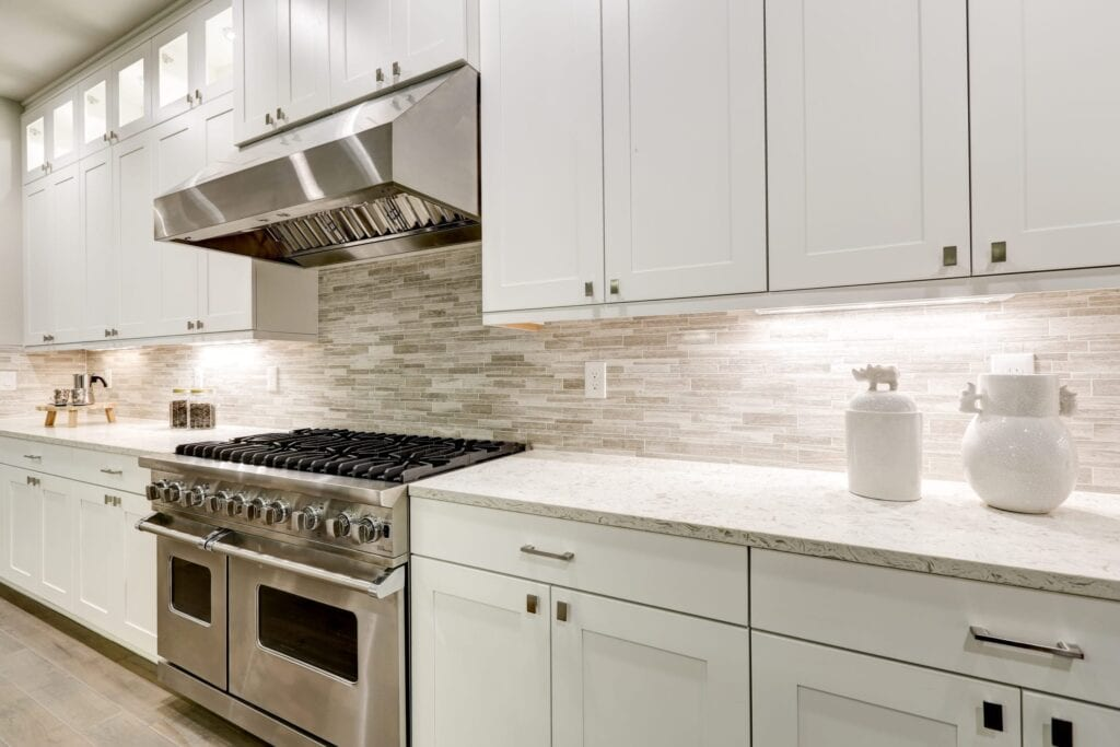 Luxury kitchen with white cabinets and stainless steel oven
