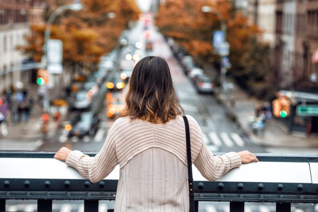 girl on a bridge overlooking city