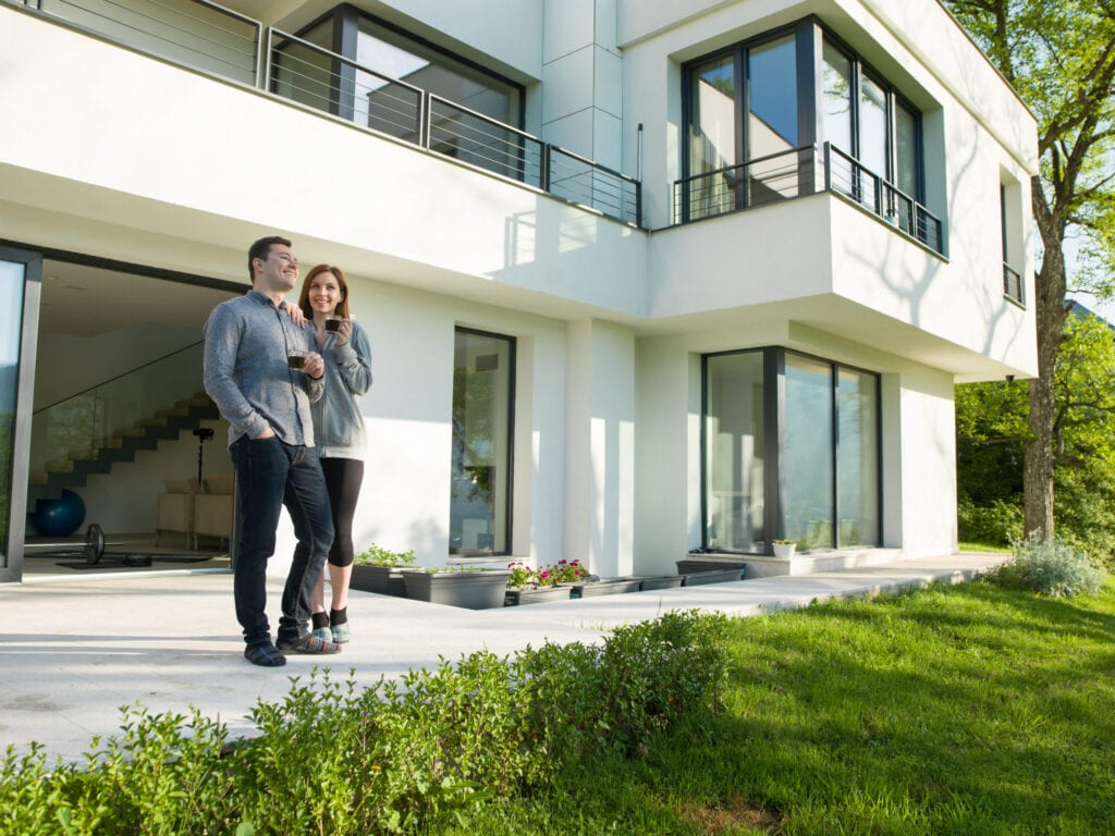 couple in front of modern home