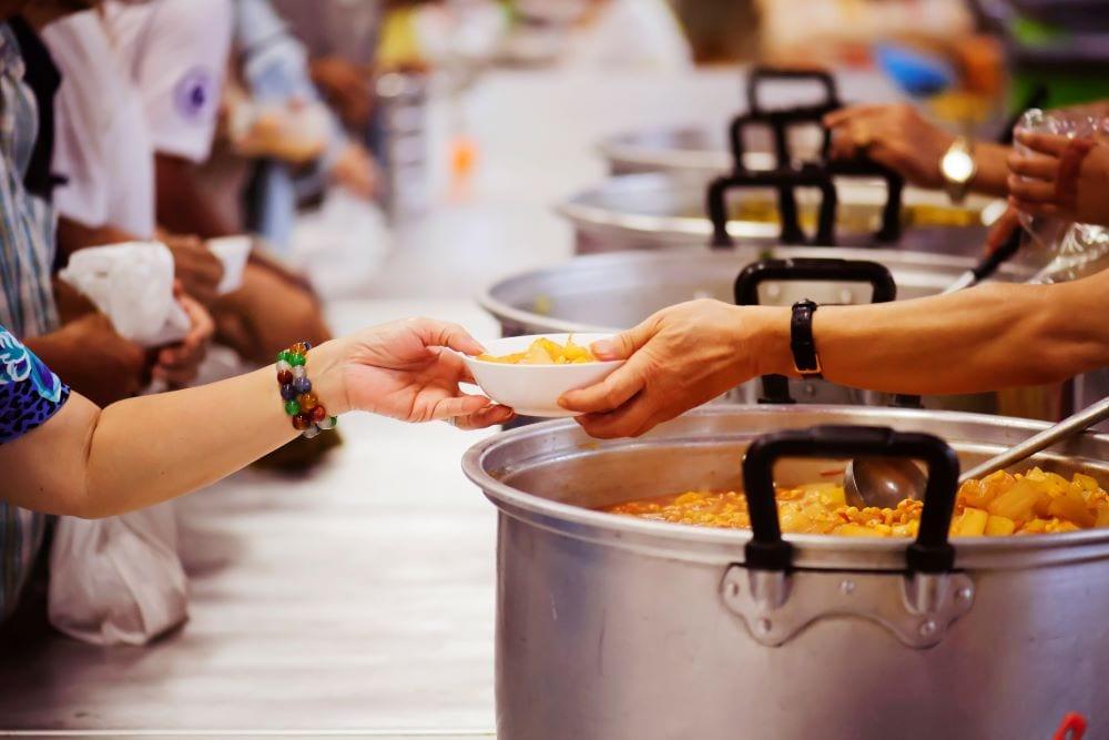 soup kitchen, handing person a bowl of soup