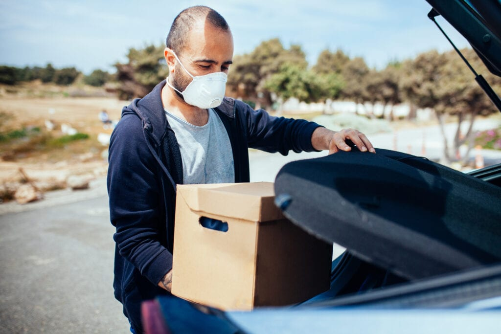 Man carrying box from his car, wearing protection mask