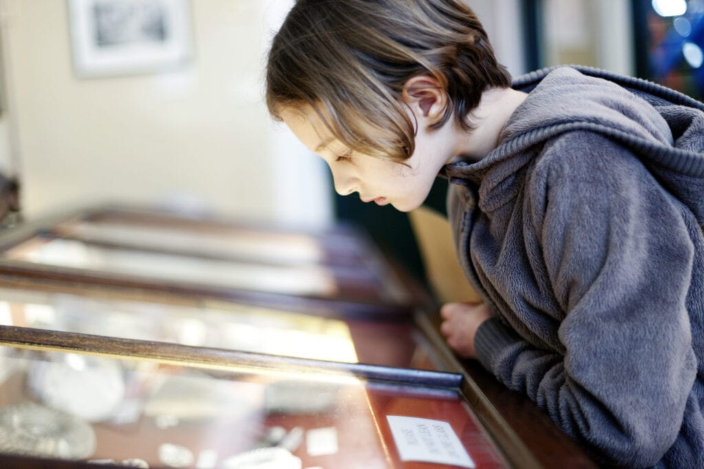 A young girl looking at an exhibit in a glass display case in a museum, Lyme Regis, Dorset, UK