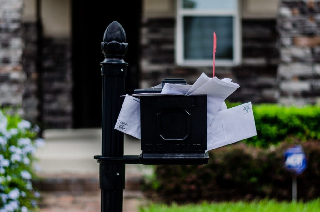 overflow mailbox with house in background
