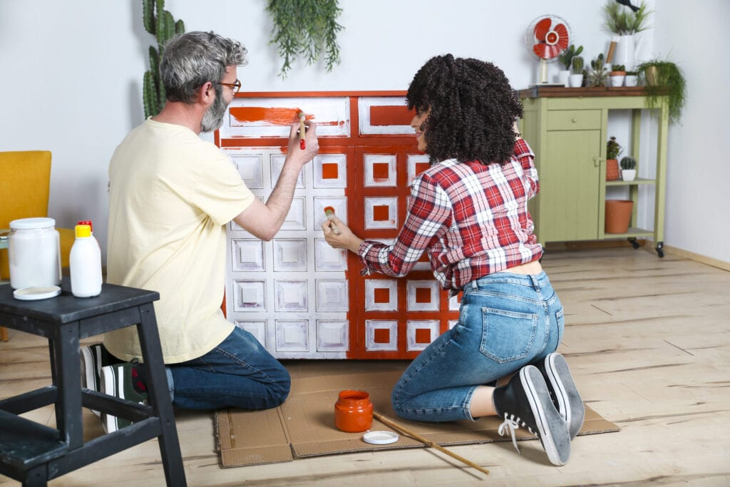 Couple painting furniture with brush at home