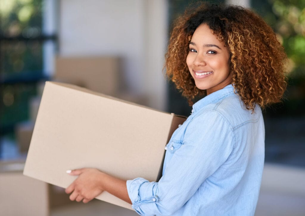 Portrait of a young woman carrying a cardboard box into her new home