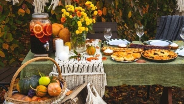 Outdoor Thanksgiving buffet with pumpkins, pie, and fall decorations