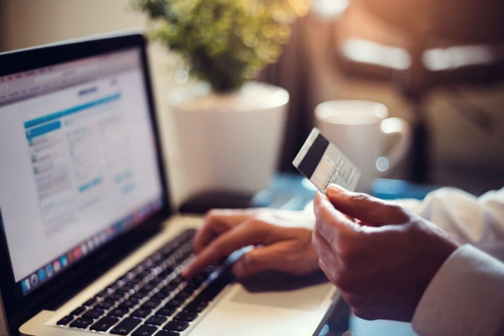 Person is online shopping for Black Friday deals, holding credit card in front of laptop screen