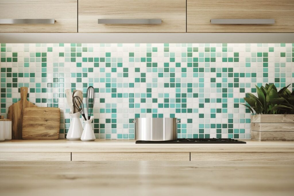 Close up of kitchen counters with green and white tile backspash