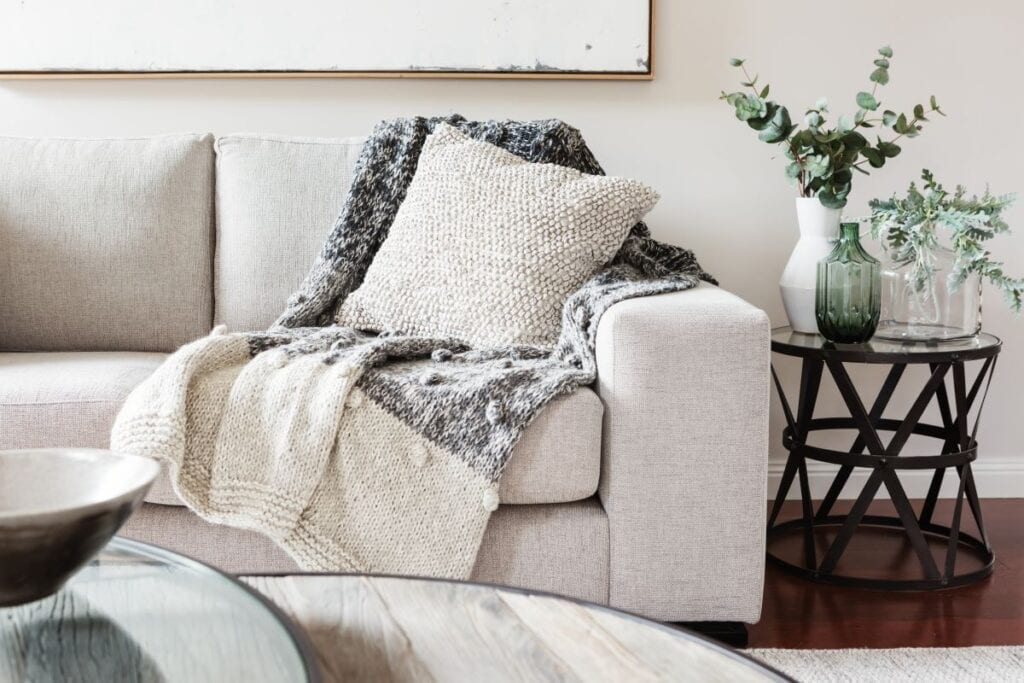 Comfortable white couch with throw pillow and blanket