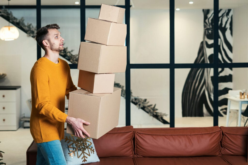 Side view of scared young adult guy move in new flat, dropping pile of boxes from hands, looking how cardboard package falling on floor
