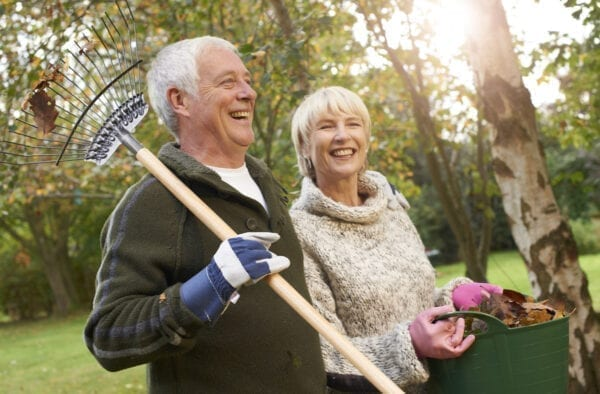 Retired couple with rake and leaves collected from the garden on a bright Autumn day.