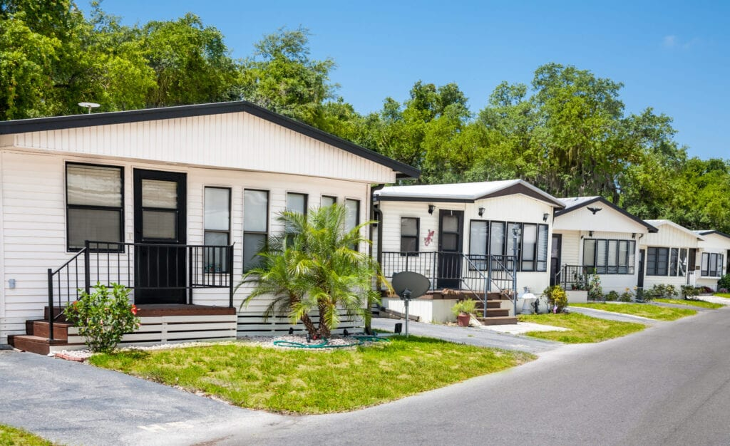 Community of mobile homes in a tropical climate; palm trees, front lawns, neighborhood. Static caravans, manufactured homes