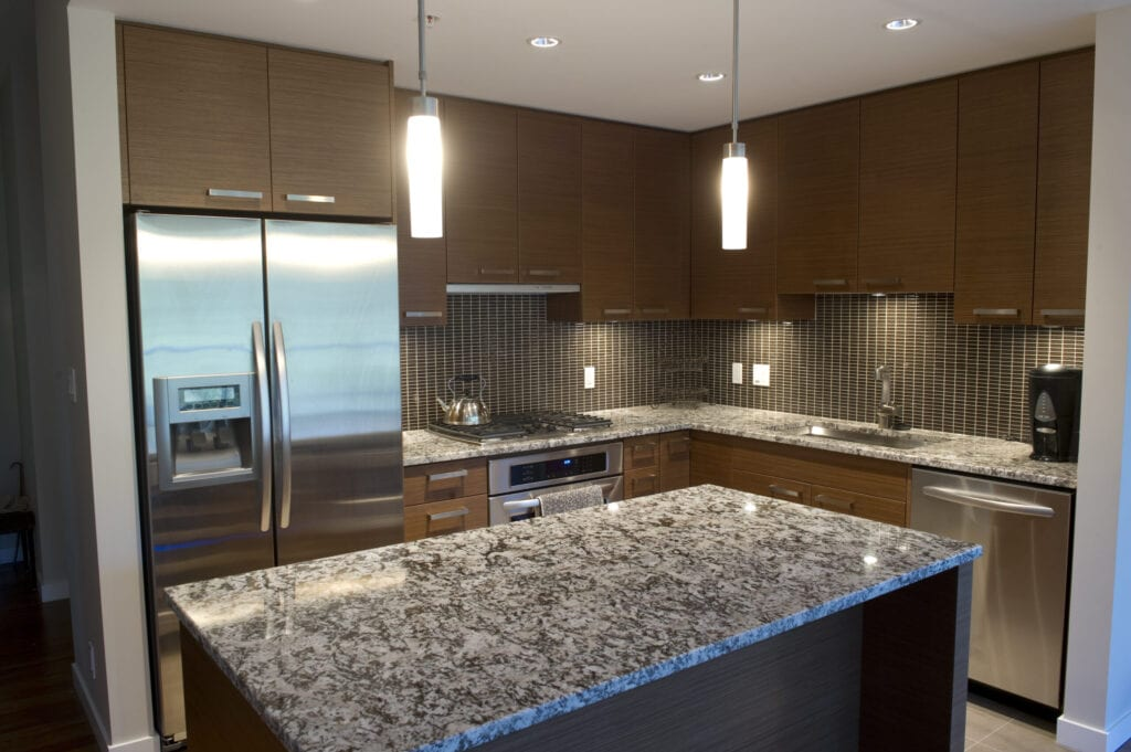 Modern luxury kitchen featuring granite counter tops and stainless steel appliances