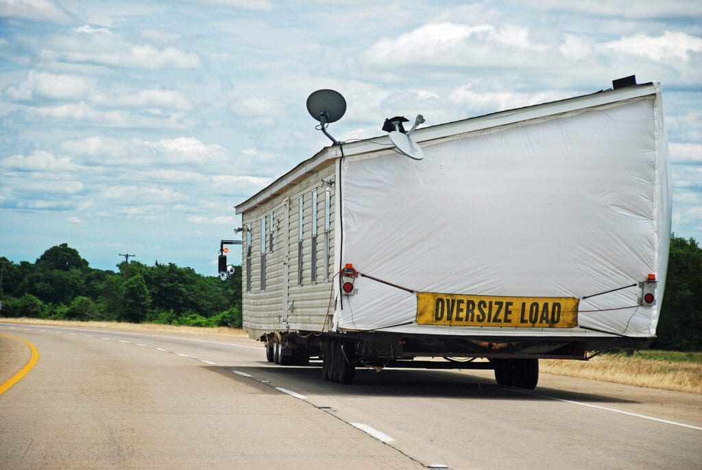 Half of double-wide house trailer being transported along interstate highway