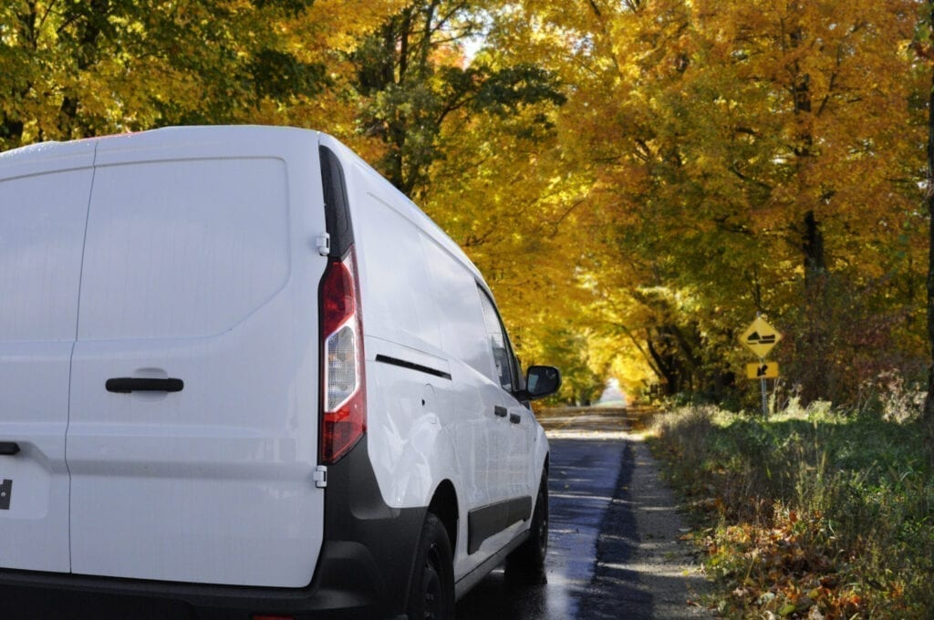 White delivery van on a rural road at the peak of autumn crossing a colorful tree tunnel