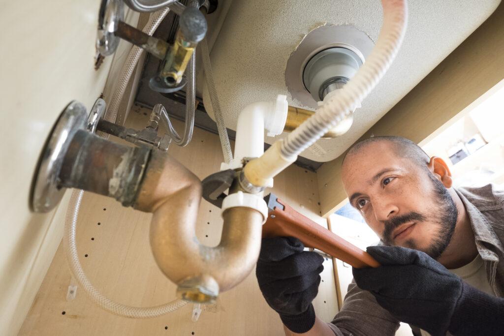 Hispanic plumber working under sink