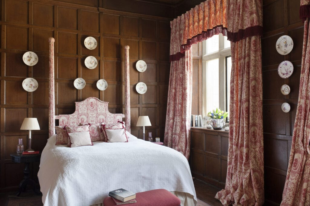 Toile de jouy curtains and bed dressings by Design Archive in bedroom with wooden wall panelling and decorative china plates