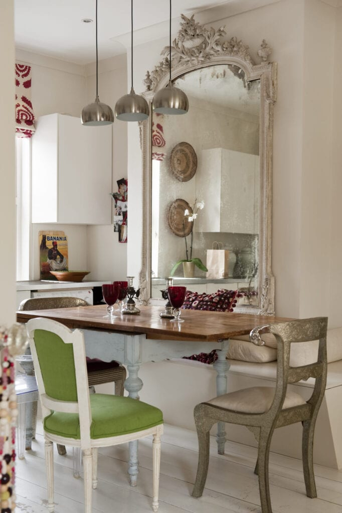Dinging room with modern silver pendant lights, large french mirror and rams head chair from Graham and Green