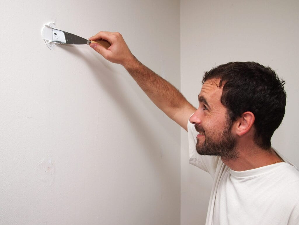 Man preparing a wall for painting. The black hair caucasian man is fixing a hole in the wall.