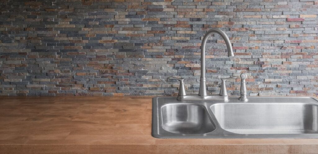 Close up of stone veneer kitchen backsplash with wood countertops and stainless steel faucet