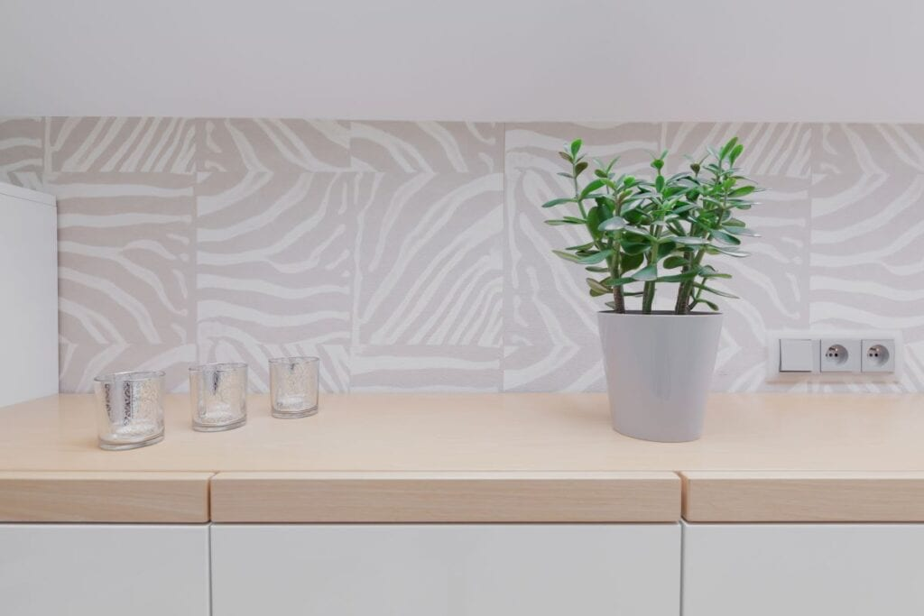 Close up of kitchen with wooden counter top and modern wallpaper patterned backsplash