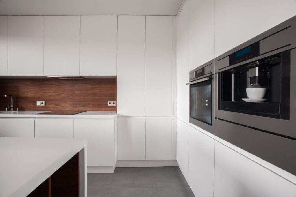 White kitchen cabinets with wood backsplash that adds contrast