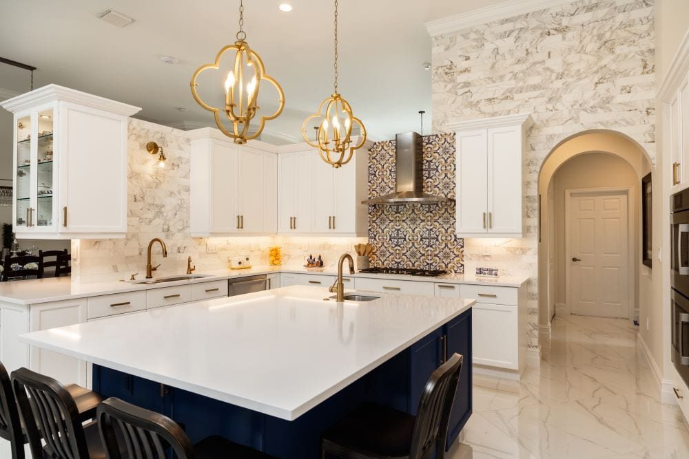 Luxury kitchen with floor-to-ceiling backsplash and gold pendant lights