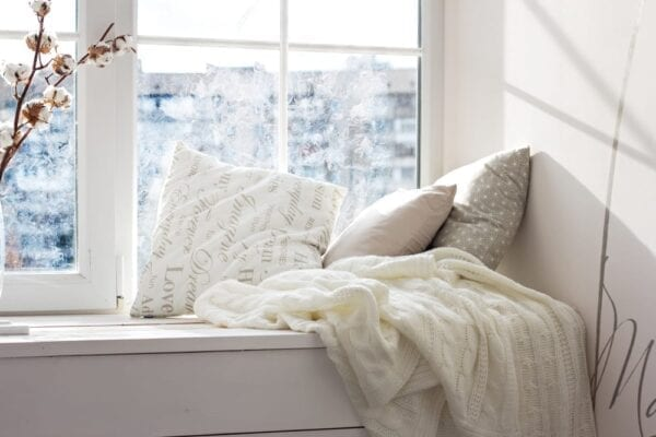 Cozy window seat with knit blankets in teen bedroom