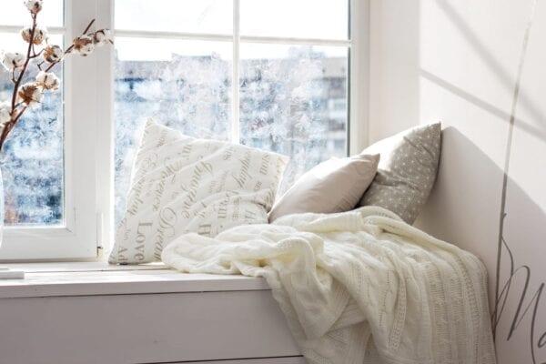 Cozy window seat with knit blankets in teen bedroom