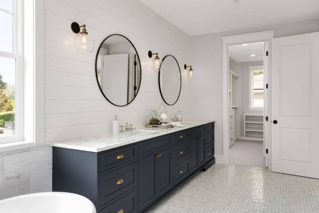 Modern bathroom with navy cabinets and brass drawer handles