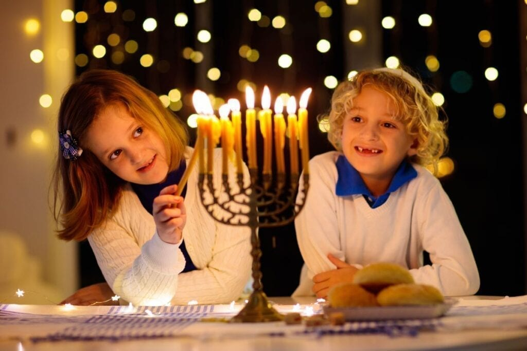 Kids lighting Hanukkah Menorah and celebrating the holiday
